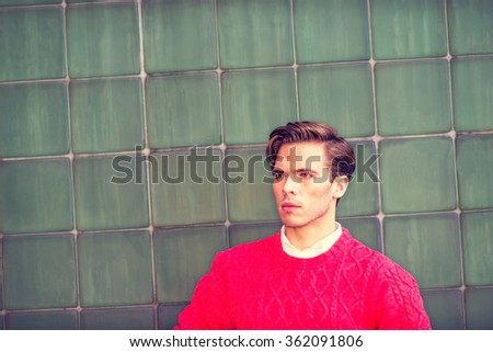 Portrait of Young Man. American college student studying in New York, wearing red knit sweater, standing by green wall, confidently looking forward, Instagram filtered effect. Copy space.  - stock photo