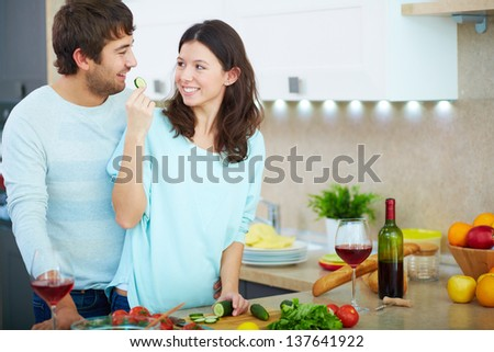 Portrait of young man and his wife cooking vegetable salad in the kitchen - stock photo