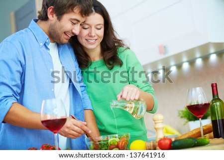 Portrait of young man and his wife seasoning salad with oil in the kitchen - stock photo