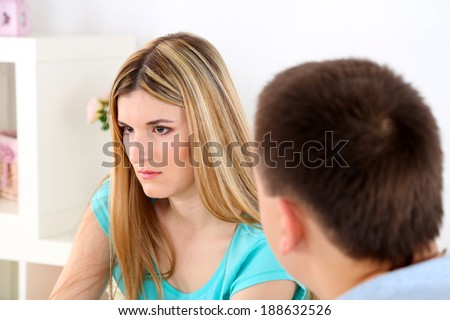 Portrait of young man and woman  conflict sitting on sofa argue unhappy, on home interior background - stock photo
