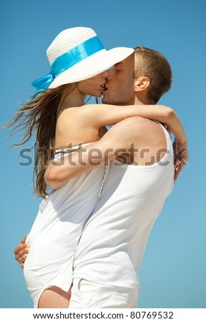 Portrait of young man and woman kissing as a happy romantic couple on a beach. - stock photo