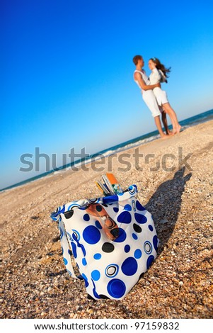 Portrait of young man and woman kissing on a beach. (Focus is on beach  bag) - stock photo