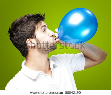 portrait of young man blowing a balloon over green background - stock photo