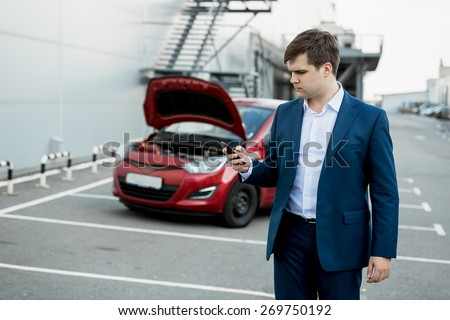 Portrait of young man calling technical car service - stock photo