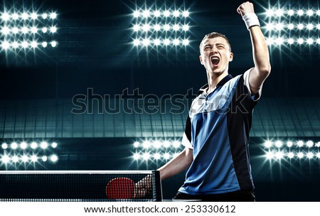 Portrait Of Young Man Celebrating Flawless Victory in Table Tennis On Dark Background with lights - stock photo
