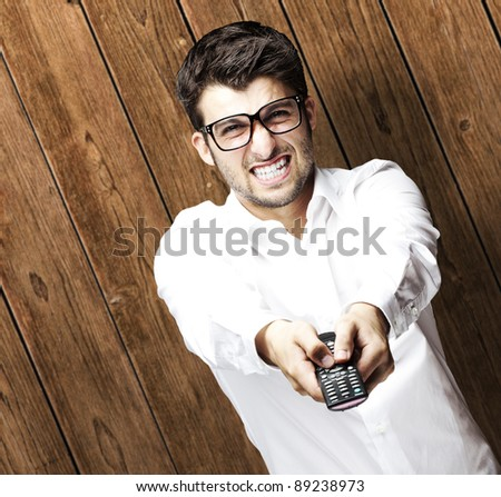 portrait of young man changing channel against a wooden wall - stock photo