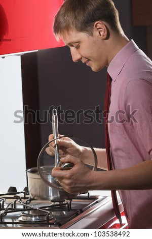 Portrait of  young man cooking soup on red kitchen