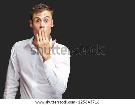 Portrait Of Young Man Covering His Mouth With Hand On Black Background - stock photo