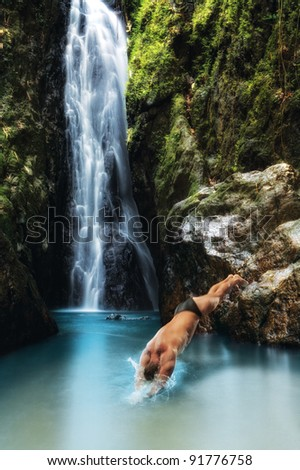 portrait of young man diving  in tropical waterfall - stock photo