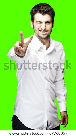 portrait of young man doing good symbol against a removable chroma key background