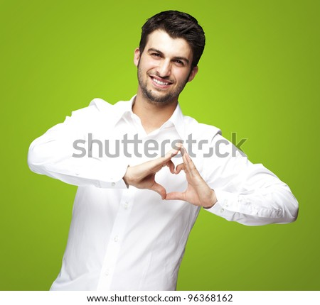 portrait of young man doing heart gesture against a green background