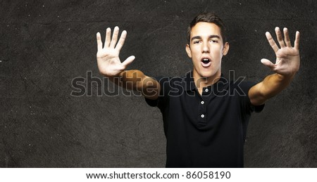 portrait of young man doing stop symbol against a vintage wall - stock photo