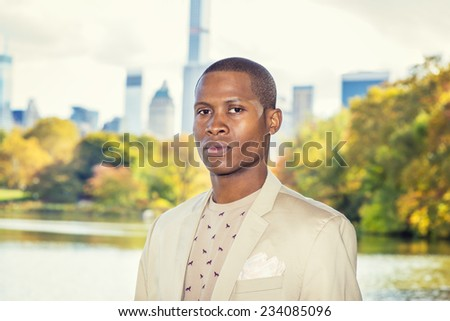 Portrait of Young Man. Dressing in cream blazer, collarless sweater, a young black guy is standing by a lake in a big city, confidently looking at you. - stock photo