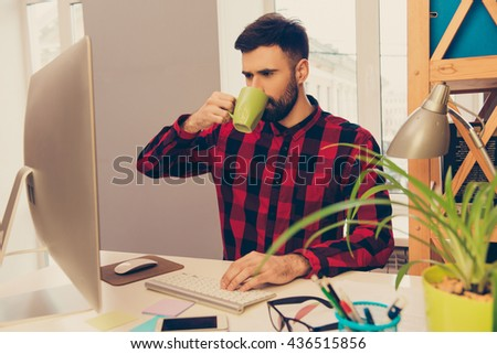 Portrait of young man drinking coffee and typing on keyboard - stock photo