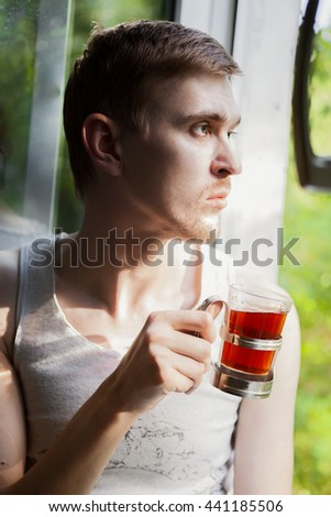Portrait of young man drinking tea near the window - stock photo