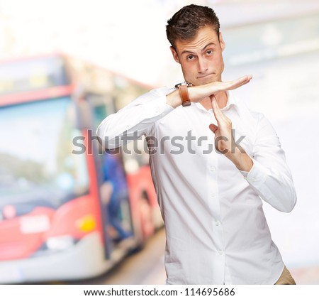 Portrait Of Young Man Gesturing Time Out Sign, Outdoor - stock photo