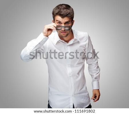 Portrait Of Young Man Giving Look While Holding Glasses On Grey Background