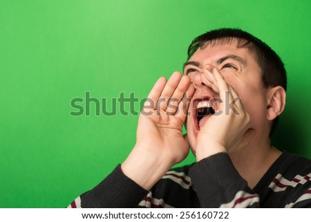 portrait of young man handsome shouting  over green background - stock photo