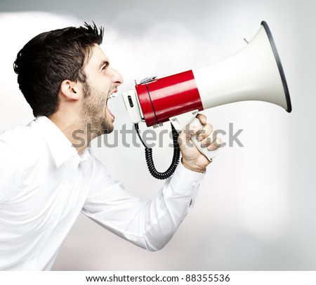 portrait of young man handsome shouting using megaphone indoor - stock photo