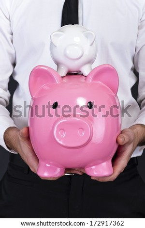 portrait of young man holding a two piggy bank against a grunge background