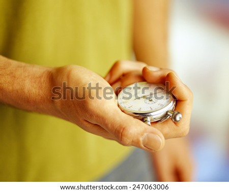 portrait of young man holding a vintage stopwatch against - stock photo