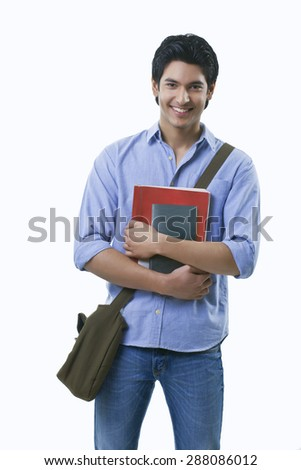 Portrait of young man holding books over white background - stock photo