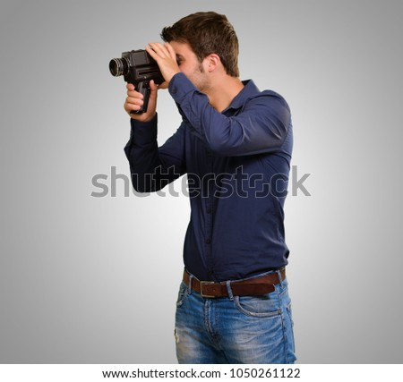 Portrait Of Young Man Holding Camera On Grey Background