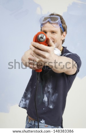Portrait of young man holding drill as gun in unrenovated house - stock photo