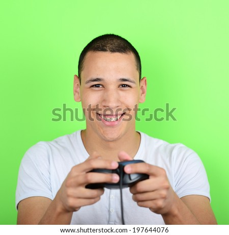 Portrait of young man holding game controller and playing games against green background - stock photo