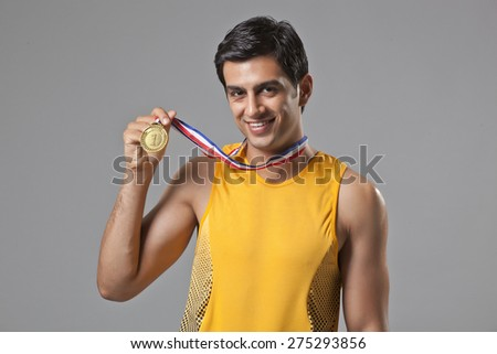 Portrait of young man holding gold medal isolated over gray background - stock photo