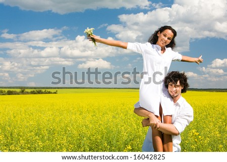 Portrait of young man holding his happy girlfriend on hands - stock photo