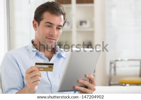 Portrait of young man holding tablet pc and credit card.indoor - stock photo