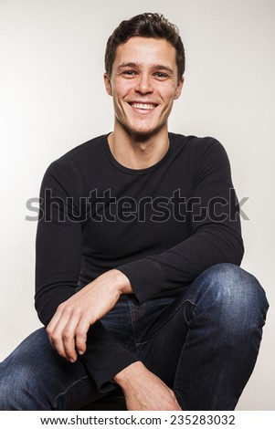 Portrait of young man in black shirt sitting on chair - stock photo