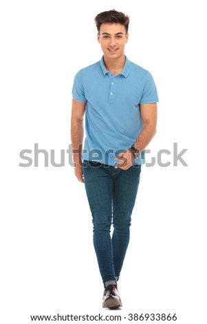 portrait of young man in blue shirt walking to the camera in isolated studio background while looking at the camera