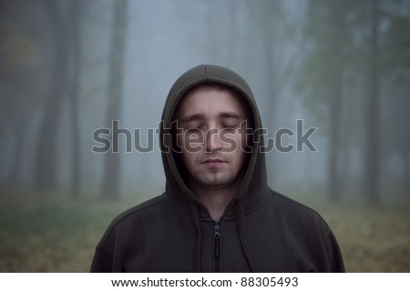 portrait of young man in forest - stock photo