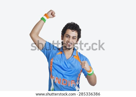 Portrait of young man in Indian cricket team jersey cheering up with clenched fists over white background