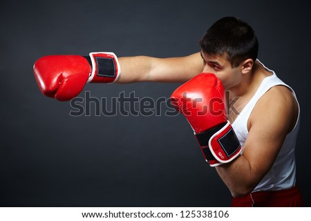 Portrait of young man in red boxing gloves fighting in isolation - stock photo