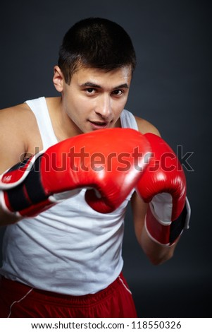 Portrait of young man in red boxing gloves looking at camera - stock photo