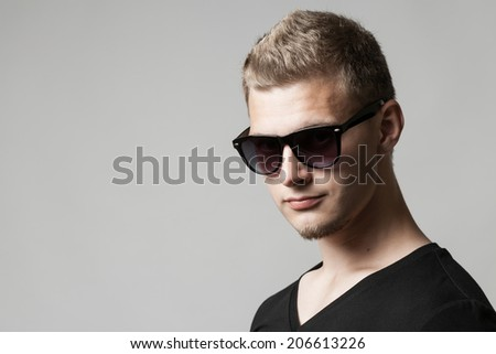 portrait of young man in sunglasses isolated on gray background with copyspace
