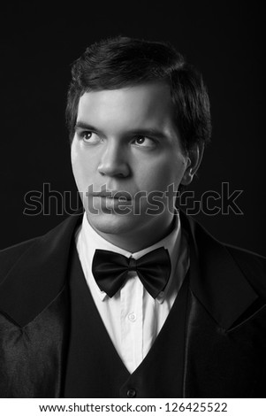portrait of young man in tuxedo isolated on black background - stock photo