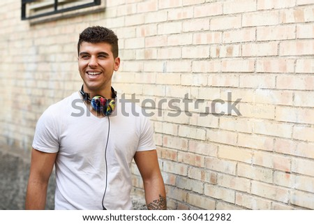 Portrait of young man in urban background smiling with headphones. Wearing white t-shirt near a brick wall