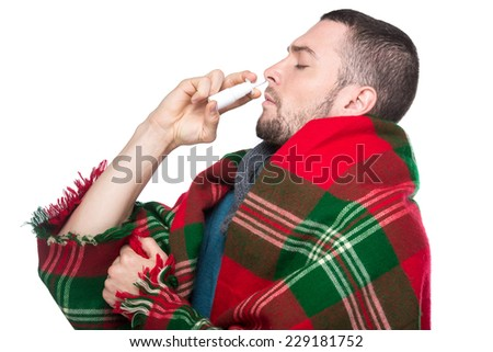 Portrait of young man is using nose spray. - stock photo