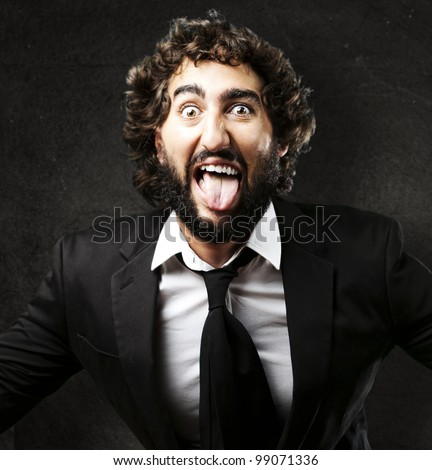 portrait of young man joking and showing the tongue against a grunge wall - stock photo