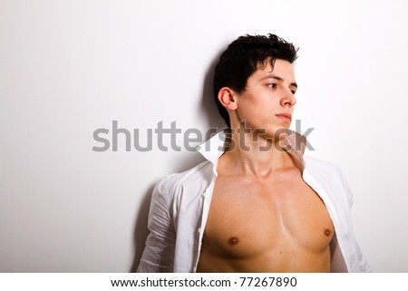 Portrait of young man leaning against a wall and thinking - stock photo