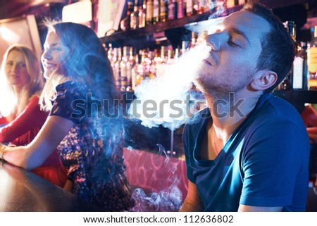 Portrait of young man letting smoke out of nostrils while smoking hookah - stock photo