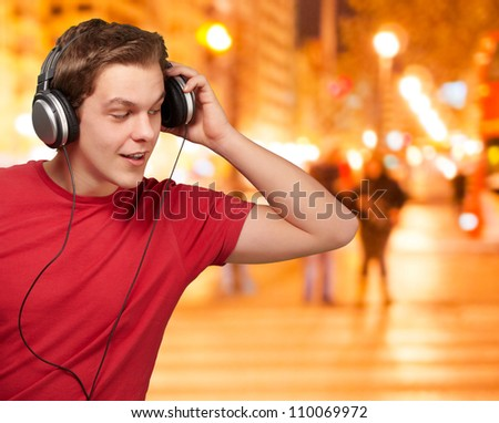 portrait of young man listening music at night city