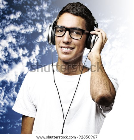 portrait of young man listening to music against a blue sky background