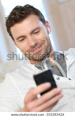 Portrait of young man listening to music with smartphone - stock photo