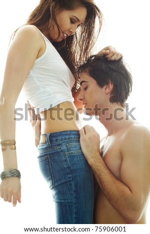 Portrait of young man looking at his girlfriend?s belly while she touching his hair - stock photo