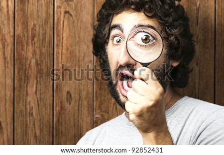 portrait of young man looking through a magnifying glass against a wooden wall - stock photo